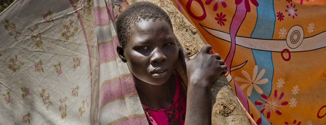 "Uganda / South Sudanese refugees / Dzaipie Reception Centre / A girl standing on the ""dorway"" of her family makeshift shelter, under the tree. Walk around Dzaipi transit centre in northern Uganda and you will see thousands of children running about, tents full of pregnant women, young mothers and newborns, and elderly women resting against trees. What you do not see are many men. Women and children make up the vast majority of the nearly 50,000 people who have fled fighting in South Sudan to become refugees in neighbouring Uganda. Many have been made widows and orphans by clashes between forces loyal to President Salva Kiir and his former deputy Riek Machar, as well as by other conflicts in the world's youngest state since early 2012. / UNHCR / F. NOY / January 2014"